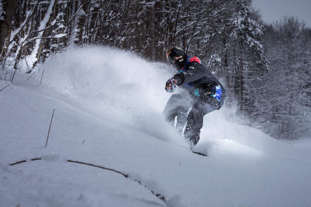 Snowboarder spraying snow on a powder day