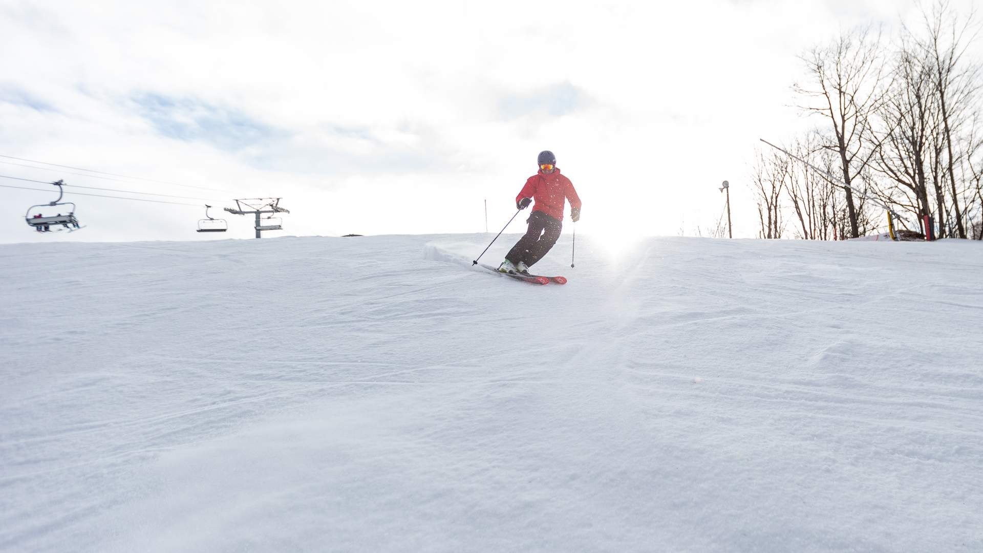 Male skier in a red jacket carving a turn at the top of the ski hill with the chairlift in the background